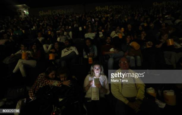 A young woman uses her cell phone during previews before the start of the James Bond film ÔSkyfallÕ at the Shell Open Air cinema at Gloria Marina on...