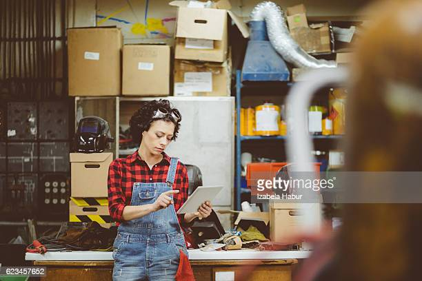 Young woman using a digital teblet in a workshop