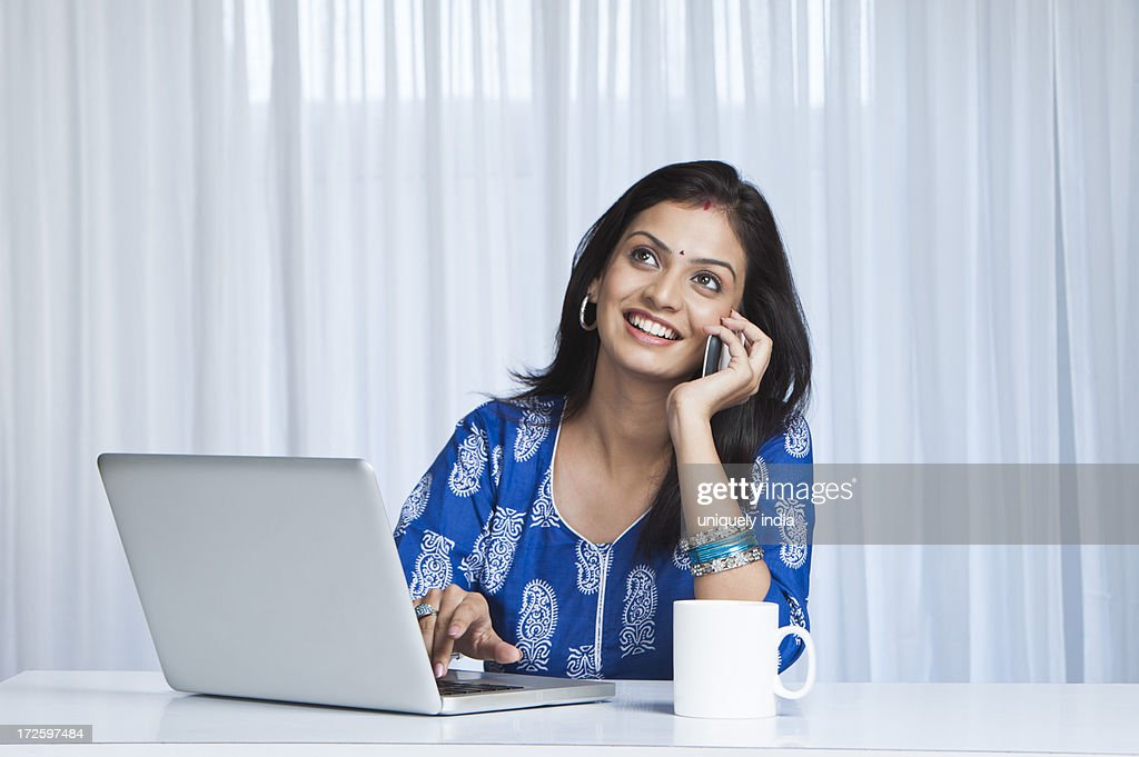 Young woman using a laptop and talking on a cell phone : Stock Photo