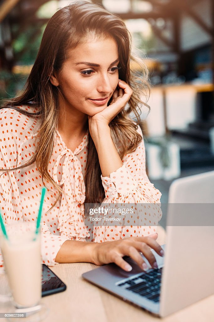 Young woman using a laptop at the cafe : Stock Photo