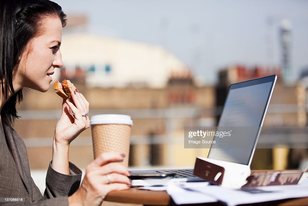 Young woman using a laptop outside while eating a sandwich : Stock Photo