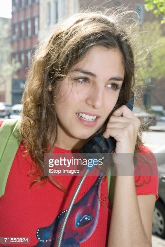 Young woman using a pay phone : Stock Photo