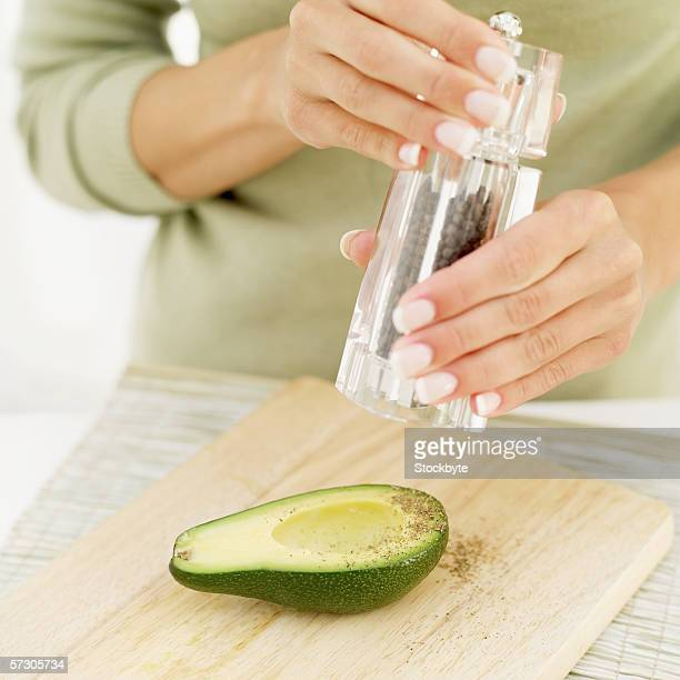 Young woman using a pepper mill over half an avocado