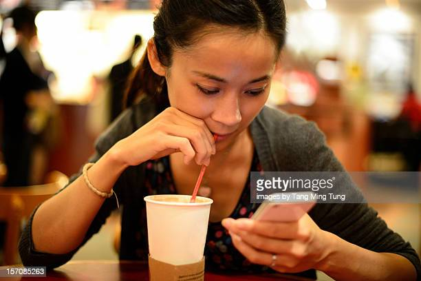 Young woman using a smart phone in coffee shop