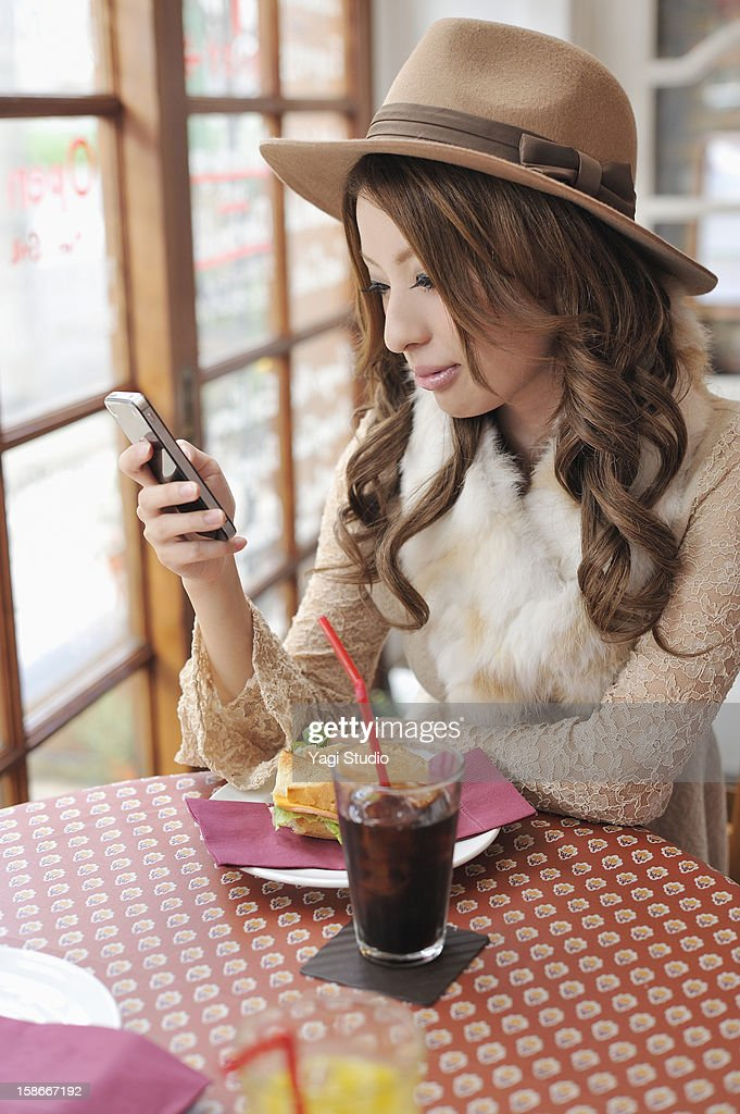 Young woman using a smartphone in the cafe : Stock Photo