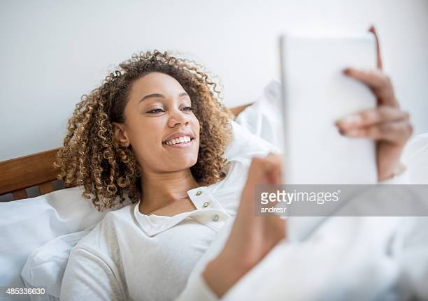 Young woman using a tablet in bed