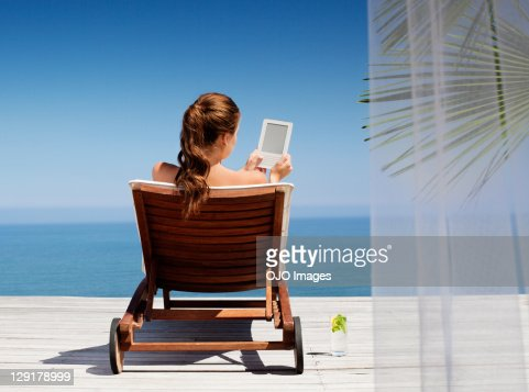 Young woman using an electronic reader while sitting on deck chair : Stock Photo