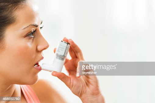 Young woman using asthma inhaler.