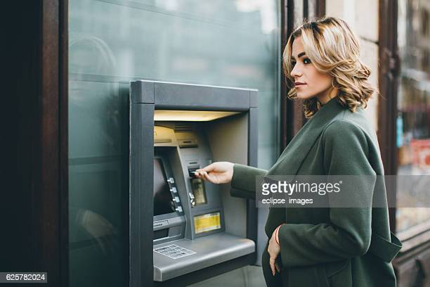Young woman using ATM