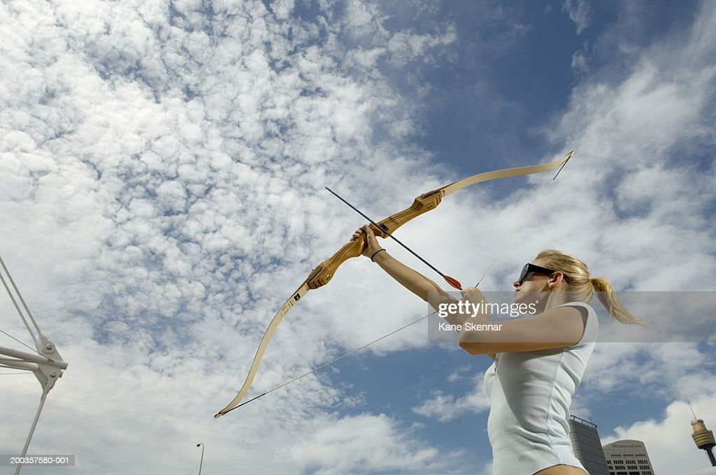Young woman using bow and arrow, side view, low angle