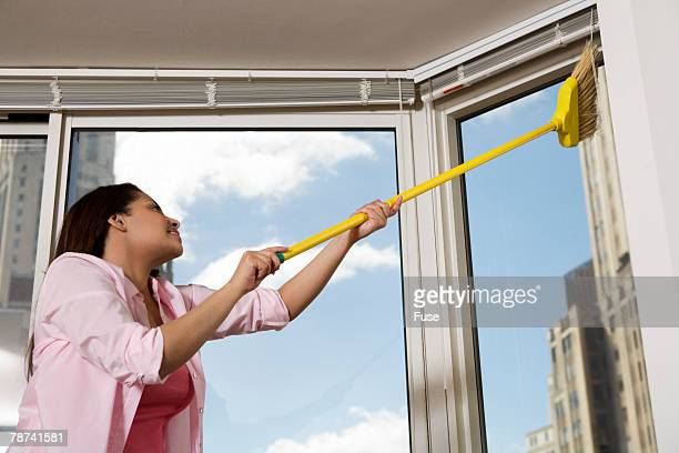 Young Woman Using Broom to Dust Top of Window Frame