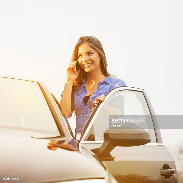 Young woman using cell phone and driving luxury black car