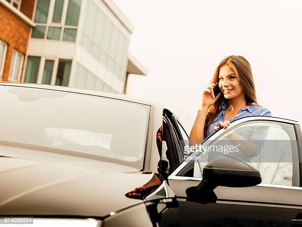 Young woman using cell phone and driving new car
