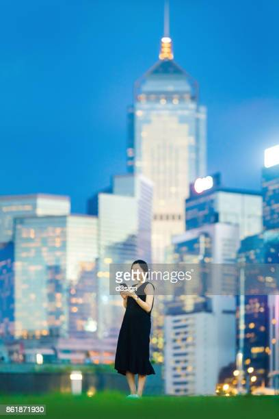 Young woman using cell phone in dynamic and prosperous financial district area in Central, Hong Kong