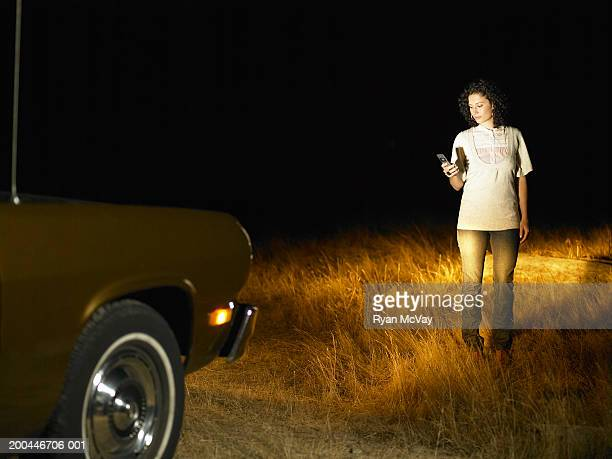 Young woman using cell phone in front of parked car, night