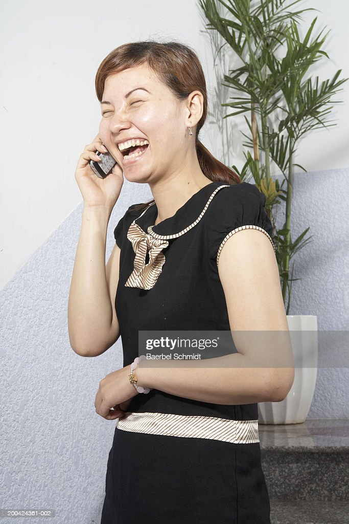 Young woman using cell phone, smiling : Foto de stock