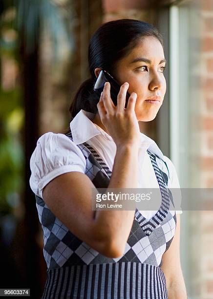Young woman using cellular phone in office