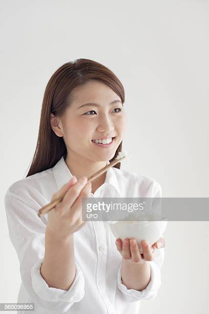 Young woman using chopsticks to eat bowl of rice