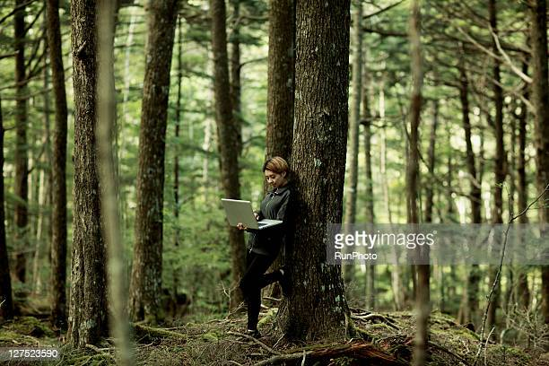 young woman using computer in the mountains