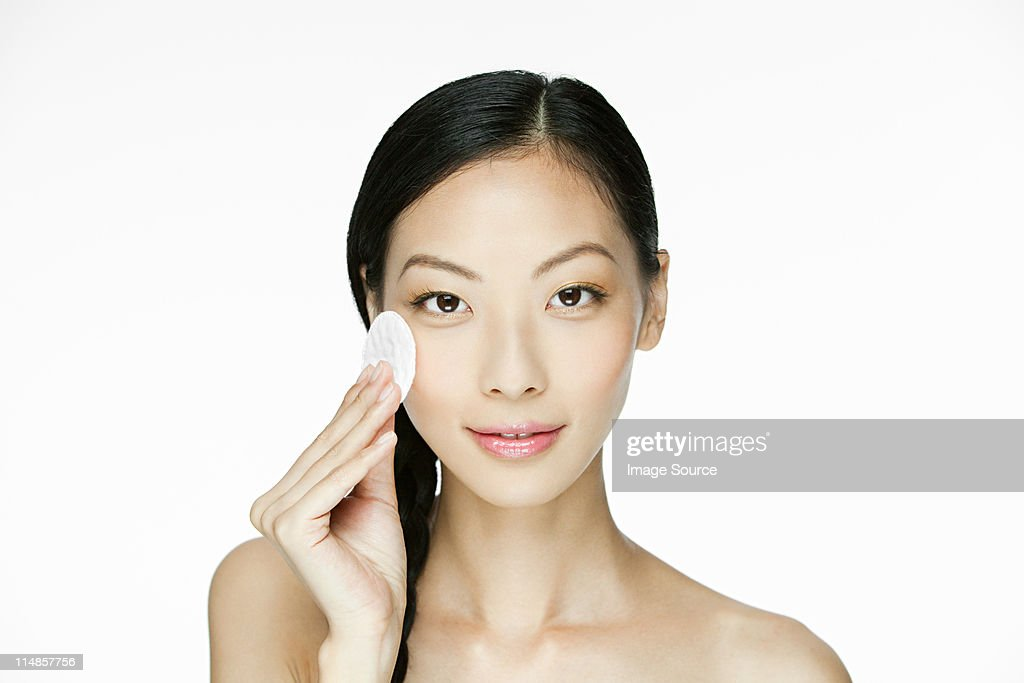 Young woman using cotton pad on face : Stock-Foto