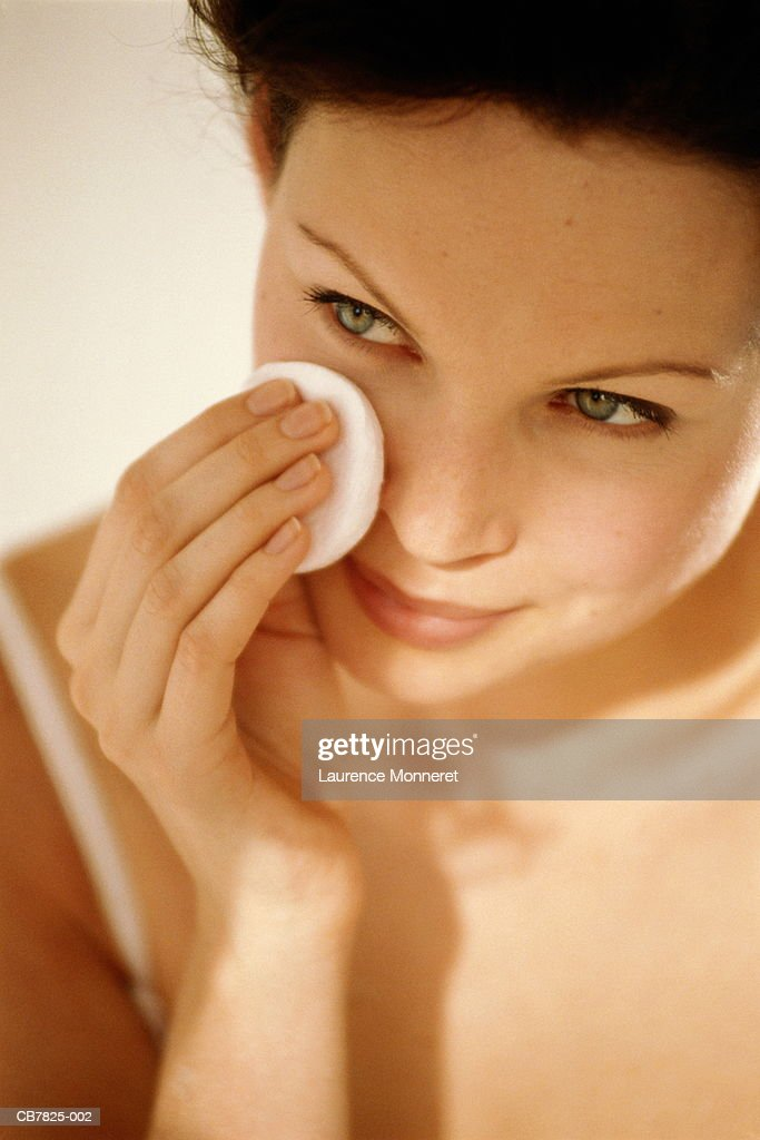 Young woman using cotton wool to wipe face, close-up : Stock Photo