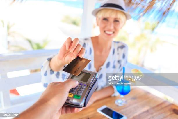 Young woman using credit card for contactless payment on beach