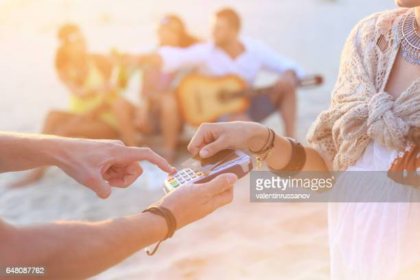 Young woman using credit card for contactless payment