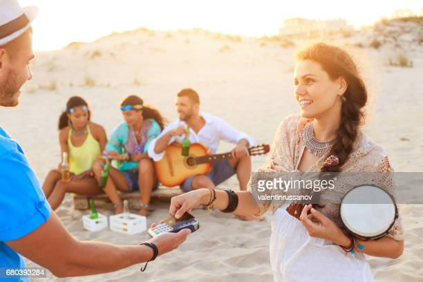 Young woman using credit card on beach
