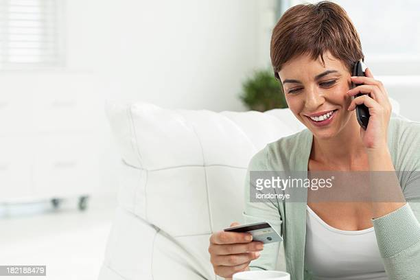 Young woman using credit card to shop over the telephone.