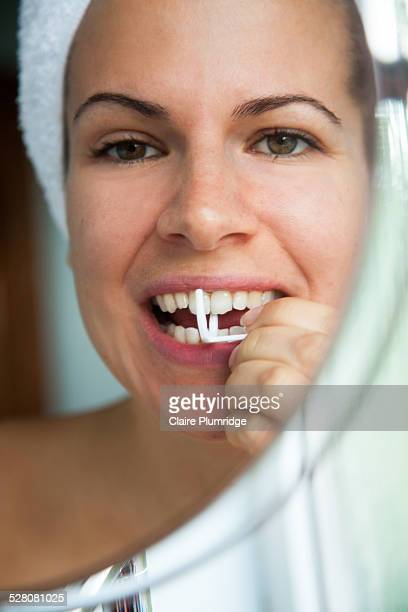 Young woman using dental flossoastline