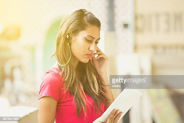 Young woman using digital tablet and listening to music
