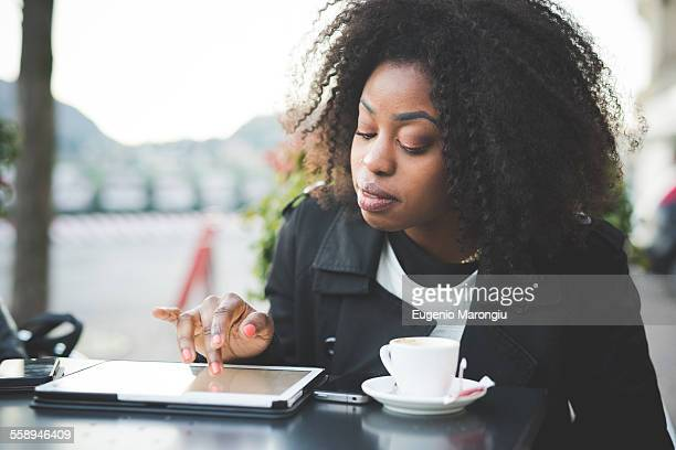 Young woman using digital tablet at sidewalk cafe, Lake Como, Como, Italy