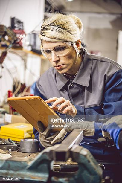 Young Woman Using Digital Tablet in Mechanical Workshop