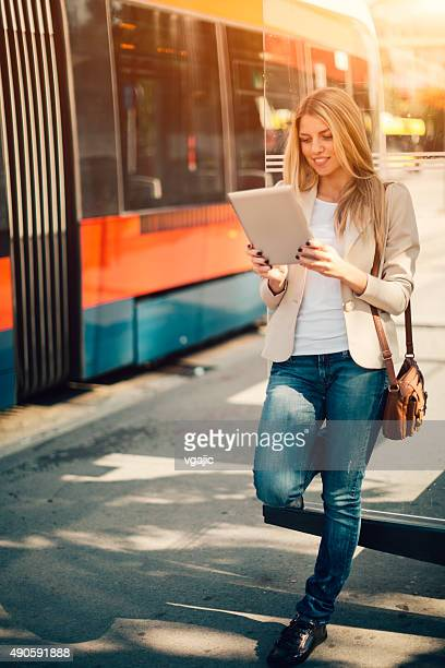 Young Woman Using Digital Tablet on Bus Station.