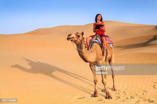 Young woman using digital tablet on camel, Rajasthan, India