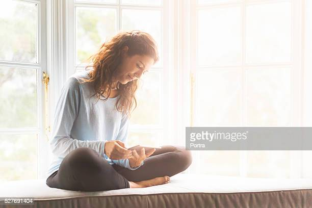 Young woman using digital tablet on window sill