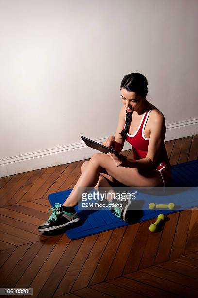 Young Woman Using Digital Tablet While Exercising