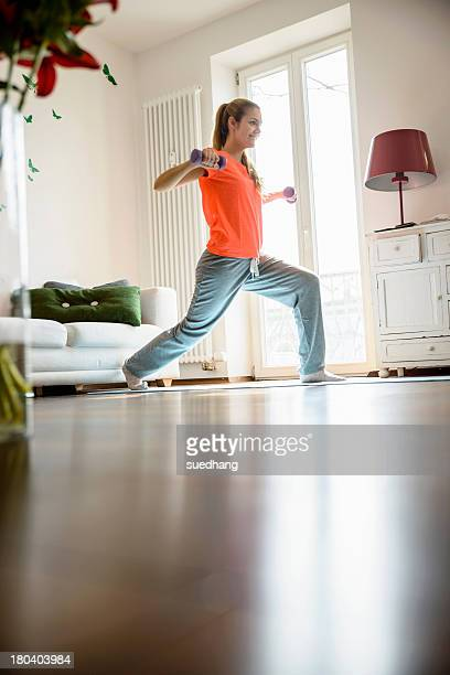 Young woman using dumb-bells at home