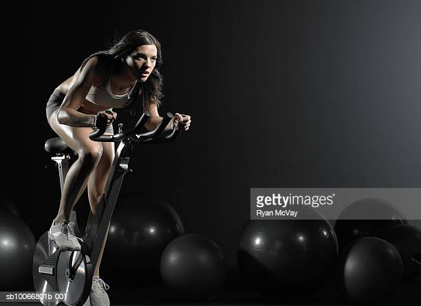 Young woman using exercise bike in gym