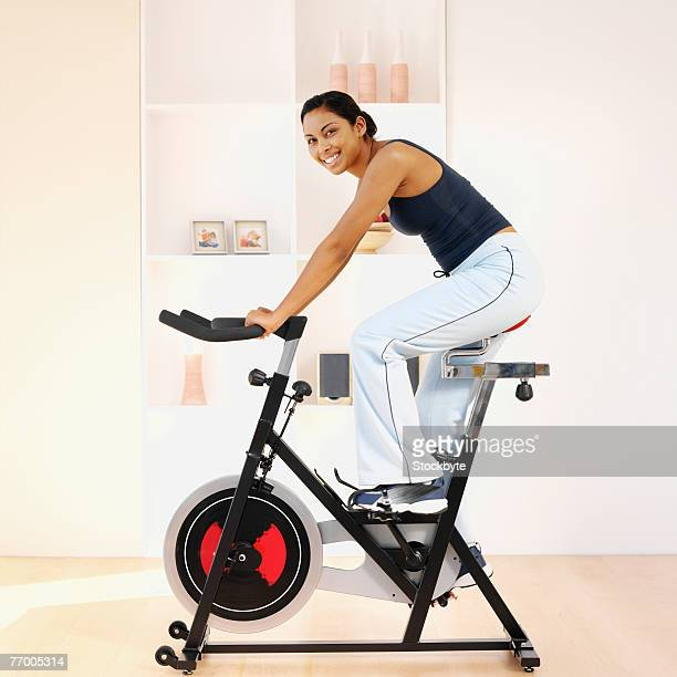 Young woman using exercise bike in home, portrait