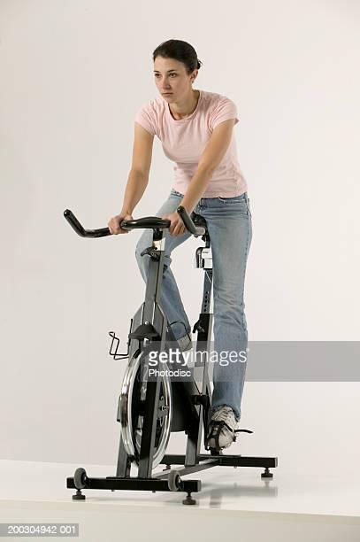 Young woman using exercise bike, posing in studio, portrait