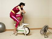 Young woman using exercising bike