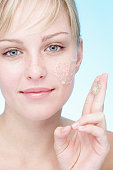 Young woman using exfoliating gel, portrait, close-up