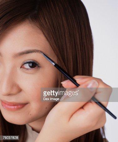 Young woman using eyebrow brush : Stock Photo
