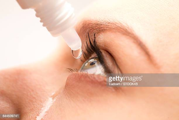Young woman using eyedrops, close-up