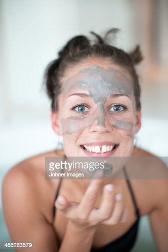 Young woman using face mask