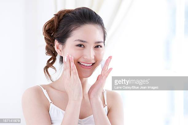 Young woman using facial cleanser to wash face