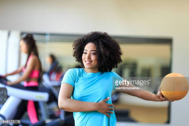 Young woman using fitness ball and stretching in gym