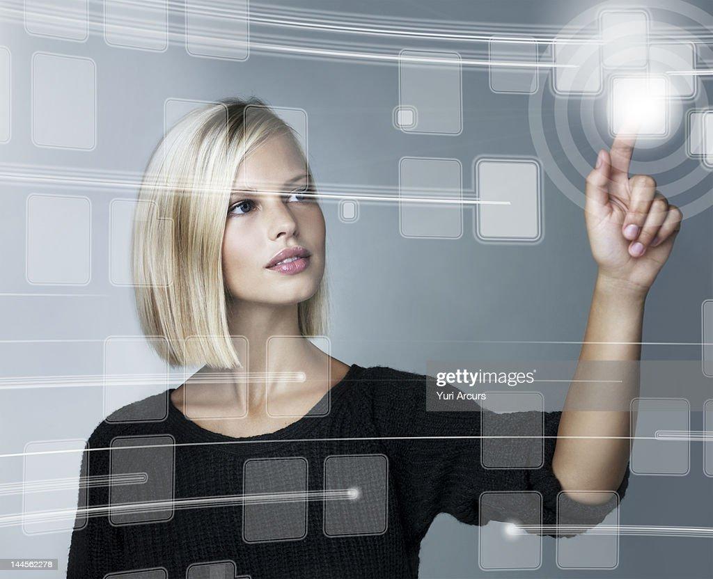 Young woman using futuristic touchscreen, studio shot
