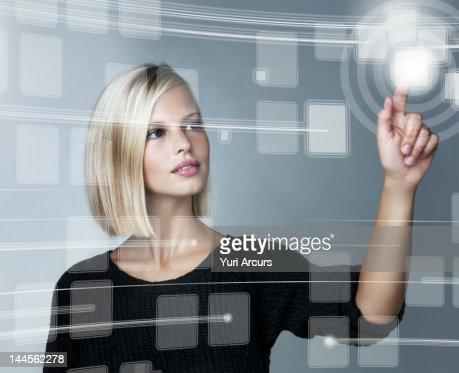 Young woman using futuristic touchscreen, studio shot